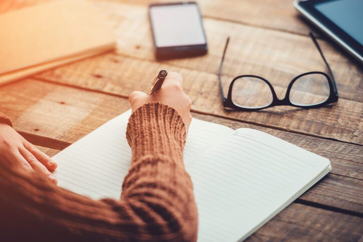 Close-up of woman writing in notebook while sitting at wooden table