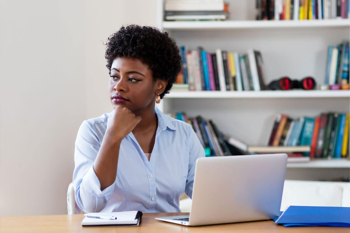 A woman stares to her right as she sits at a table with a laptop in front of her.