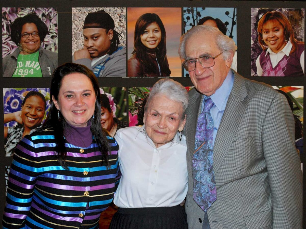 Emily Auerbach standing next to her parents smiling, in front of pictures of students