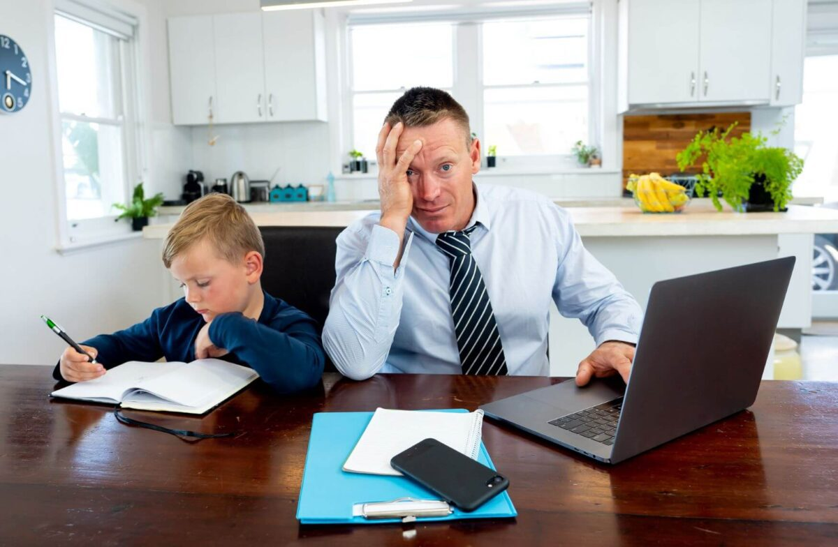 man looking frustrated as he sits next to young boy while trying to work
