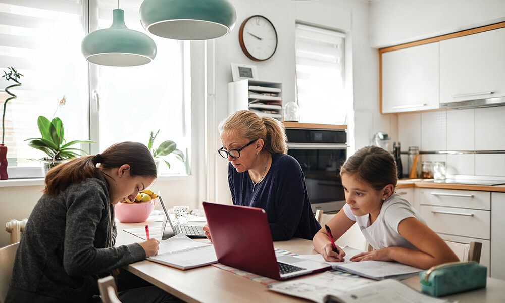 Mother and two daughters on laptops around at table at home.
