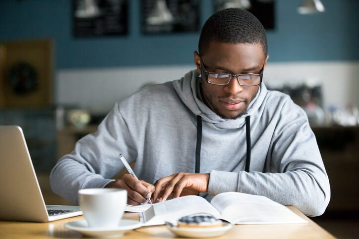 Man studying with book and laptop