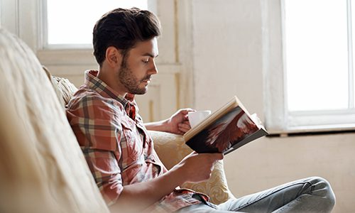 A man reads a book on his couch.