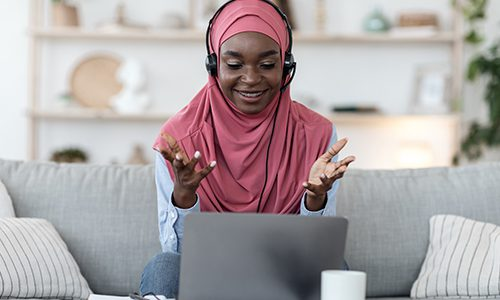 A woman in a headscarf talks animated at her computer during online class
