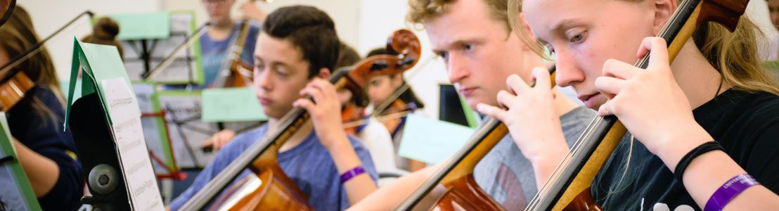 Student musicians play cellos.