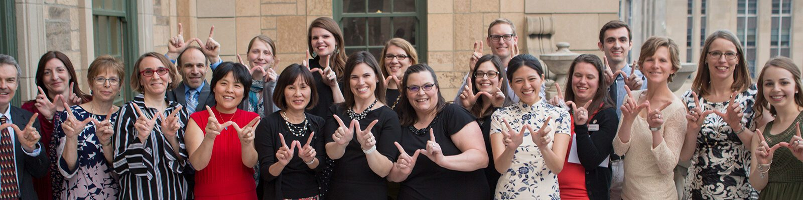 ACSSS staff make a 'W' with their hands after the Returning Student Awards Ceremony in 2018.