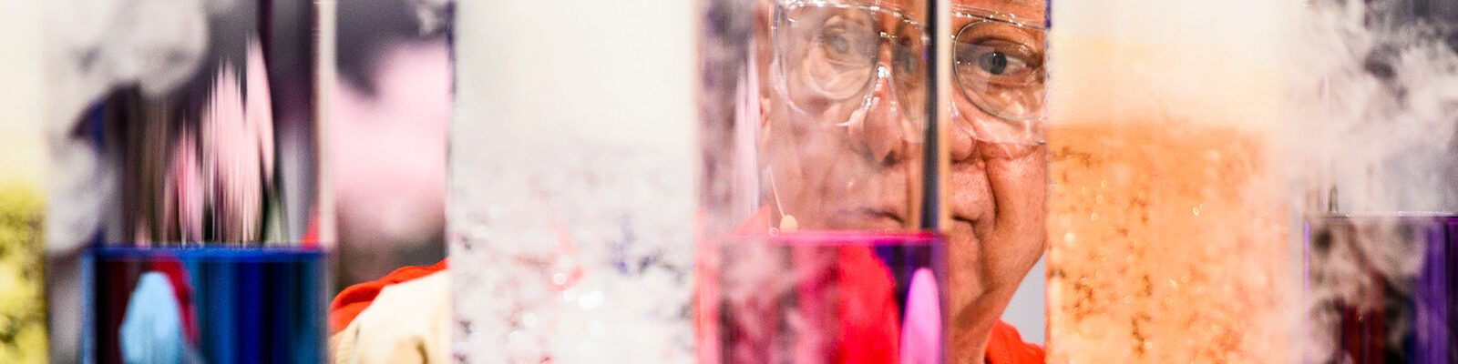 Man looks through colored test tubes