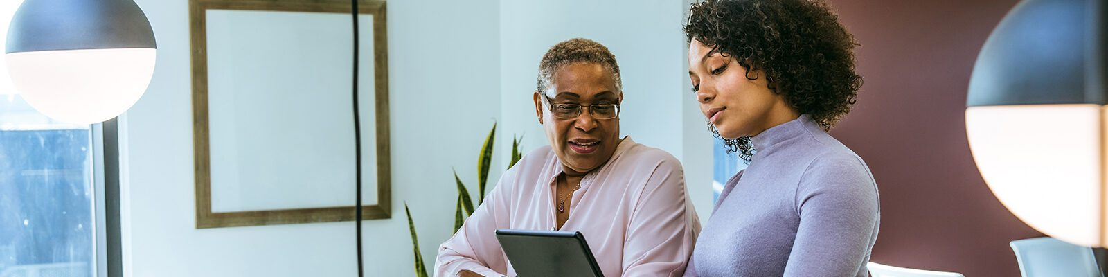 Two women look at a tablet computer