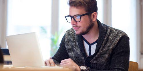 A man reading a laptop screen.