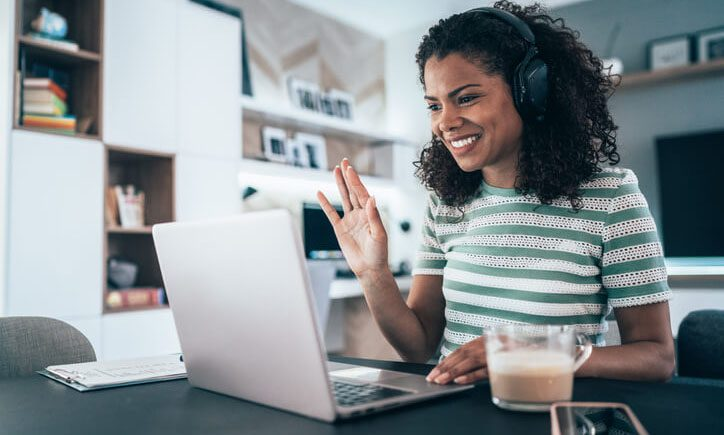 An online student waves at her classmates during a video conference.