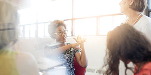 In a sunny conference room, a woman talks animatedly with her colleagues.