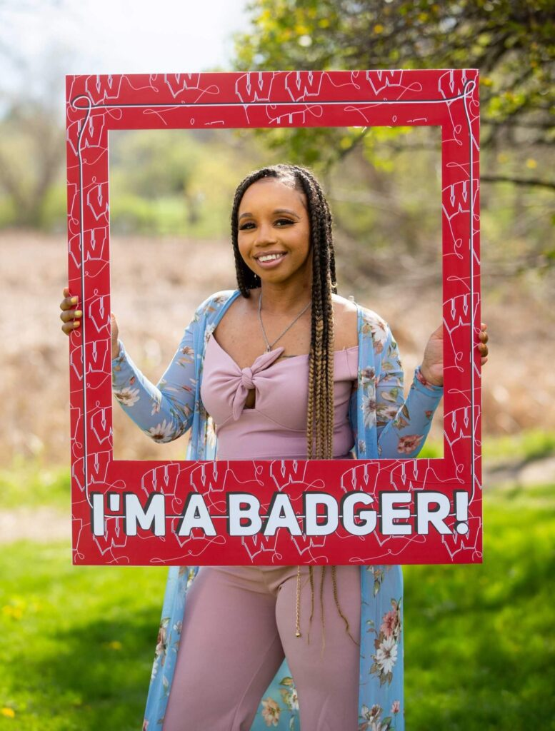Student Kewiana Pollard smiling and looking through a Badger picture frame