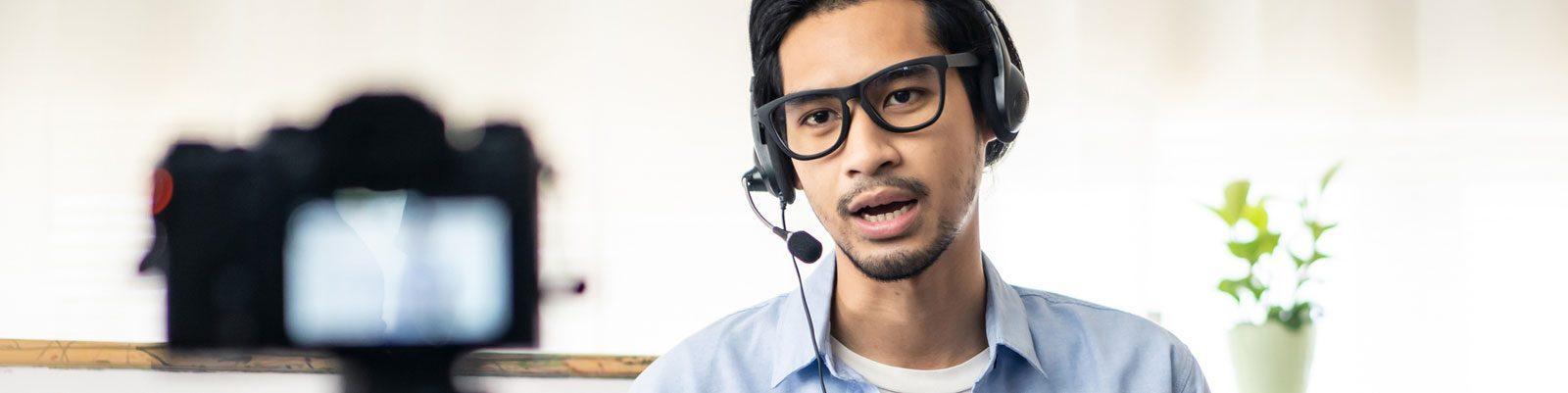 Man wearing headset speaks in front of camera