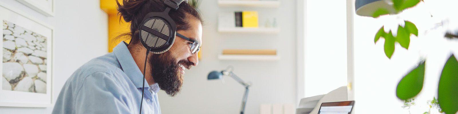 Happy man wearing headphones working on computer