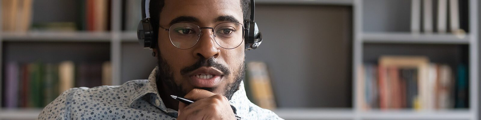 A man with headphones talks in a virtual meeting.