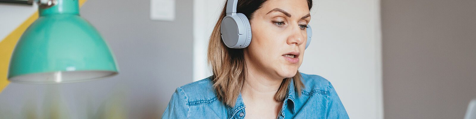 A woman with headphones talks during a virtual meeting