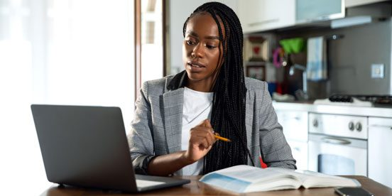 Woman interacting online while referencing notes