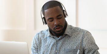Man wearing headphones taking notes next to laptop