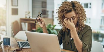 Woman working on laptop touches her face implying that she has a headache