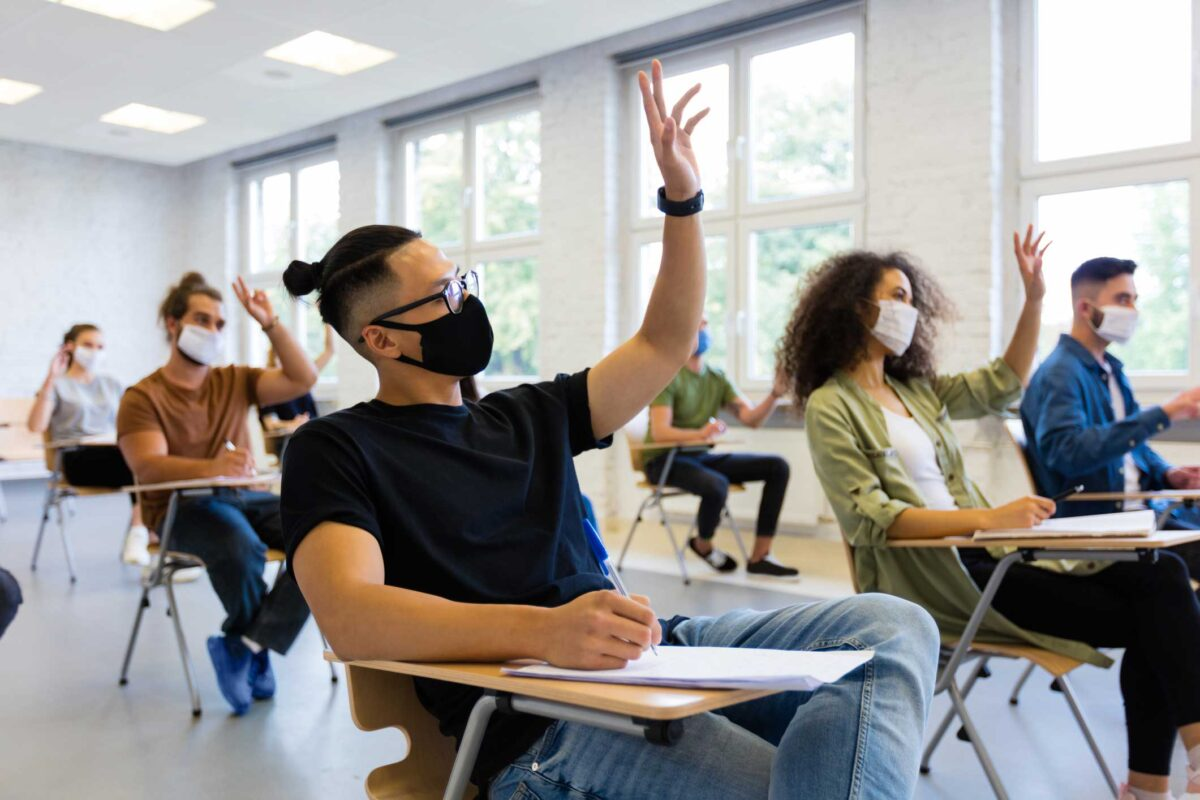 students wearing masks, in a classroom sitting down and raising their hands