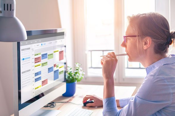 Woman pondering her schedule displayed on a computer