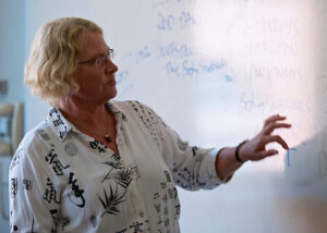 Laurie Scheer, teaching writing at whiteboard