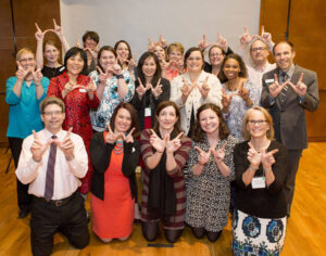 Division of Continuing Studies faculty and staff pose with the Wisconsin W hands