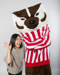 Woman waves with Bucky Badger