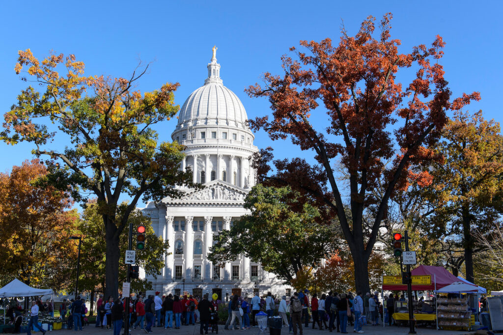 A view of the State Capitol during a fall farmers' market that is bustling with people