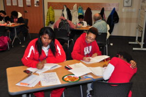 Deja Laongoen, Alayvia Jackson (right), and Maka Chikowero (foreground) work on writing projects in Odyssey Junior.
