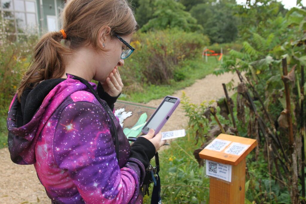 Visitors point their smartphones at QR codes on signposts, then view the information about plants and animals affected by global warming.