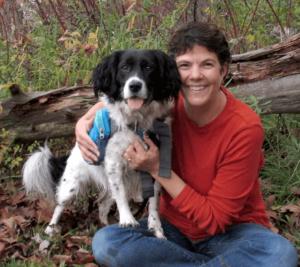 Kimberli Bindschatel huggin her dog in the woods