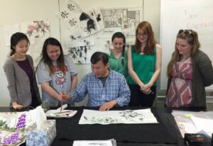 Professor Wei Dong teaches Chinese brush painting to students and community members in a University Summer Forum.