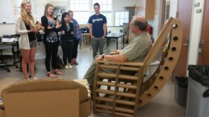 Students test a custom-designed cardboard chair.