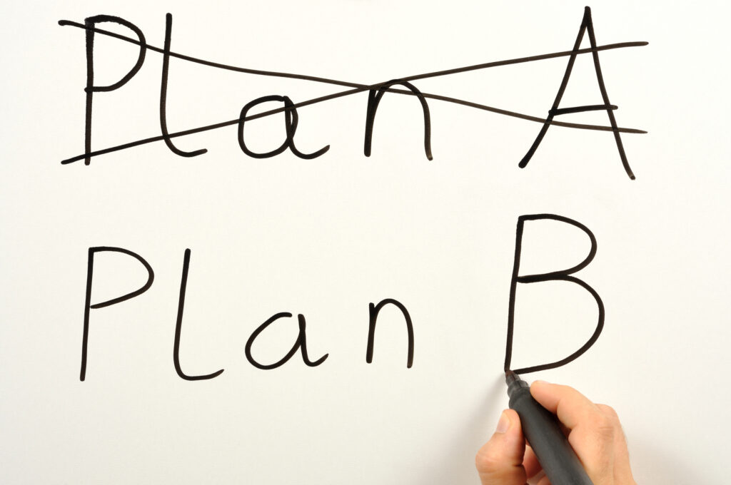 Someone writing plan A and plan B on a board
