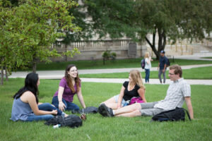 Four Summer Term students sit in the grass in Library Mall on a warm day