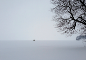 In Paula Cooper Hughes' photograph 'Bleak Fishing Hut Dark,' a tiny black hut marks the intersection of gray sky and iced-over lake.