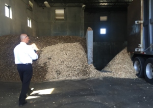 Jeff Rich discusses the wood chips (also shown above) that Envision uses in its biomass boiler.