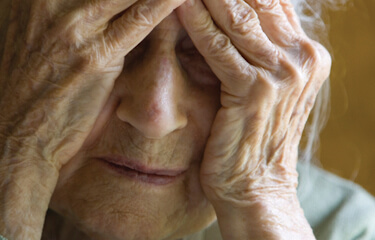 older woman with hands over her face