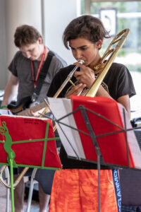 boy playing trombone with guitar player in the background