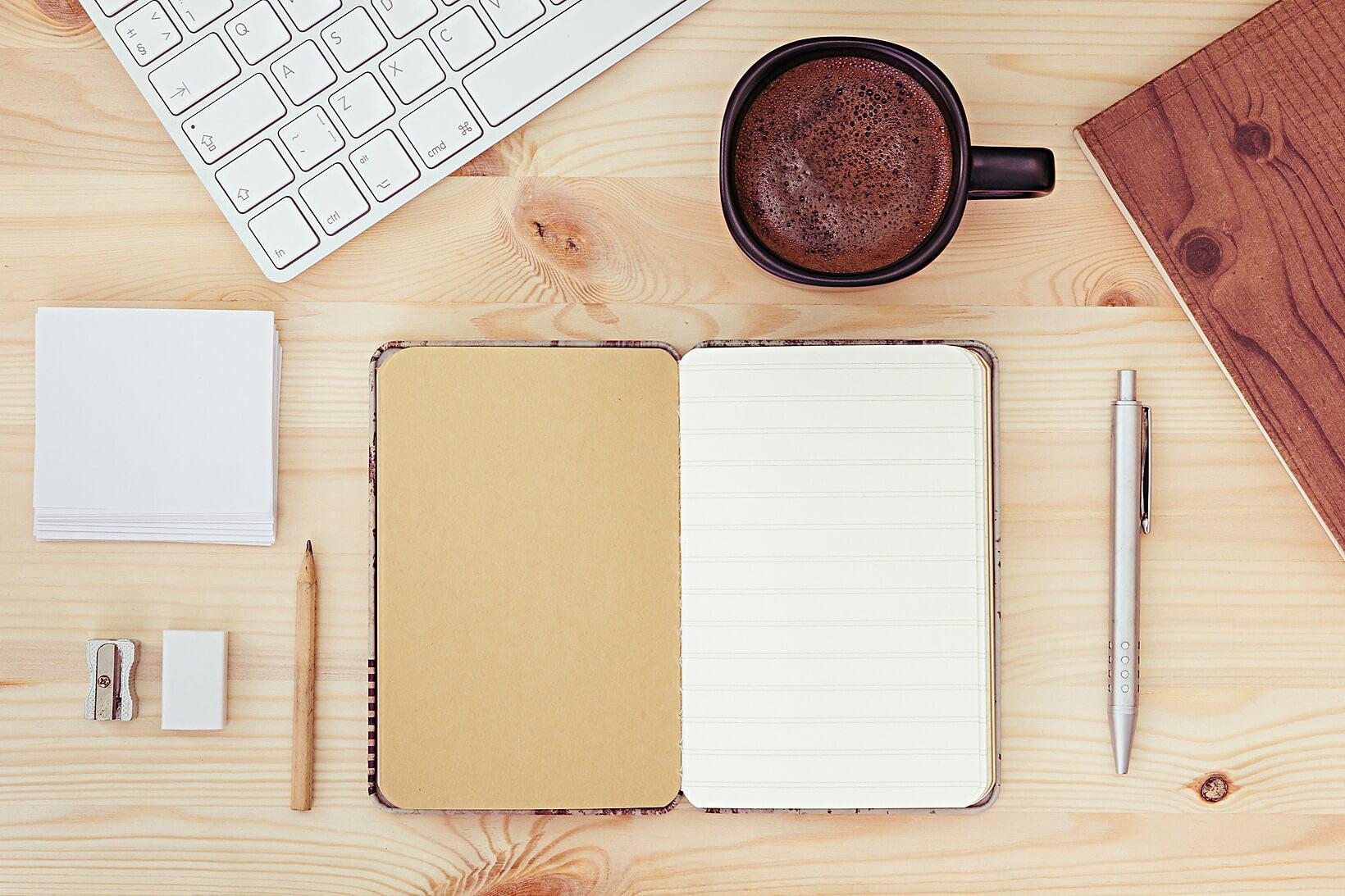 notepad, keyboard, coffee on a desktop